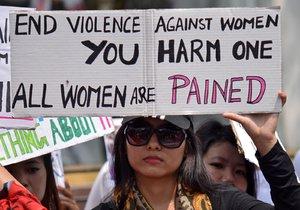 """Indická žena s transparentem v ruce protestuje proti znásilnění osmileté dívky. Na transparentu je nápis """"Konec násilí na ženách. Zranění jedné bolí všechny ženy."""""""