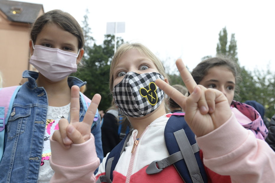 Děti čekají 1. září 2020 před Masarykovou základní školou v Újezdu nad Lesy v Praze 9 na zahájení nového školního roku. Budou v něm platit přísnější hygienická pravidla proti šíření nového typu koronaviru. Přivítal je Ministr školství Robert Plaga.