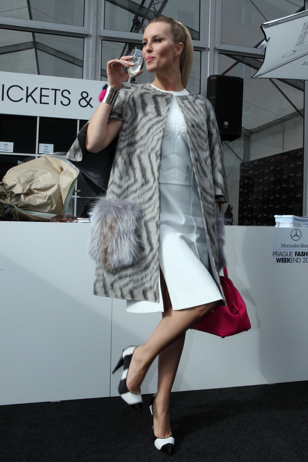 Simona Krainová: Šaty s reliéfním vlysem. Vlněný pláštík s tříčtvrtečními rukávy a efektní kožešinou na nakládaných kapsách. Glamour etuda na fúzi černé s bílou s dotyky růžové. Ukázka lady stylu konkurující eleganci Audery Hepburn a legendě snídaně u Tiffanyho.