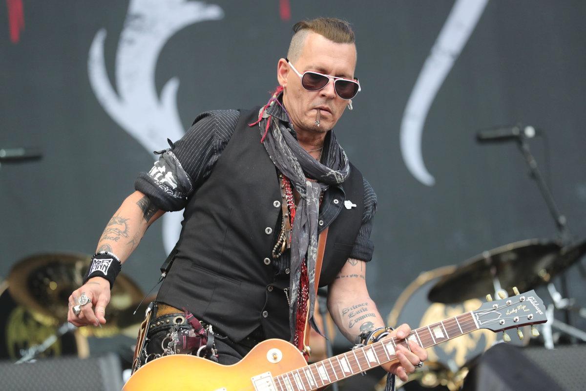 Johnny Depp na koncertu na letišti v Letňanech s vyholenou hlavou po stranách.
