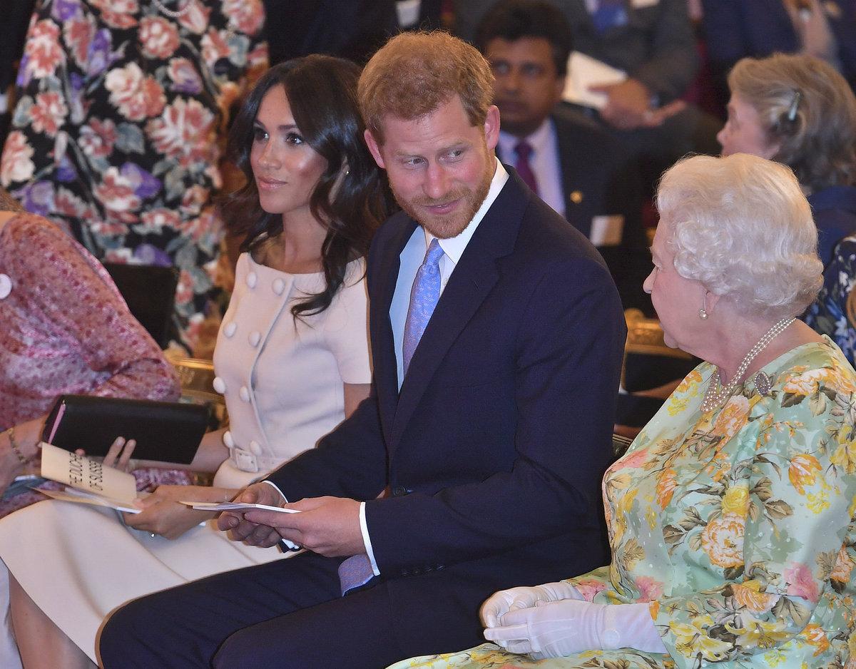 Královna Alžběta II. v doprovodu vnuka prince Harryho a jeho chotě Meghan.