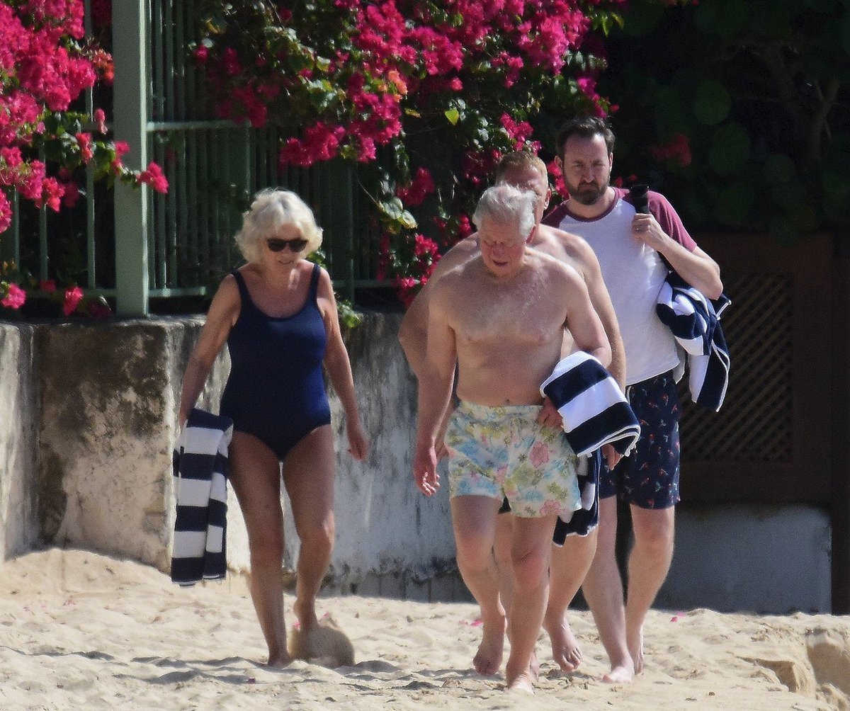 Camilla a princ Charles přicházejí na pláž.