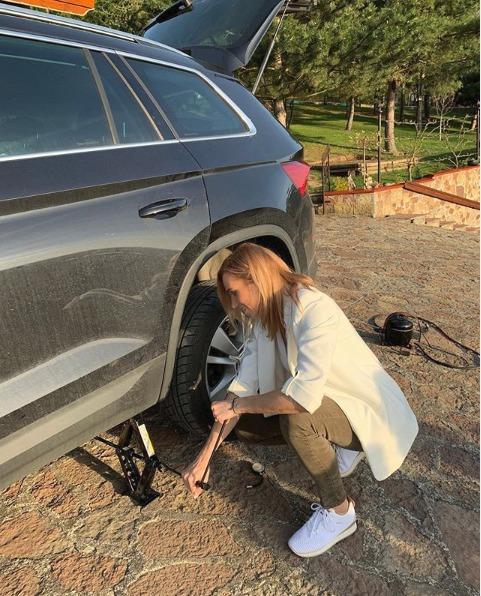 Hana Mašlíková si v bílém saku musela poradit s výměnou pneumatikou.