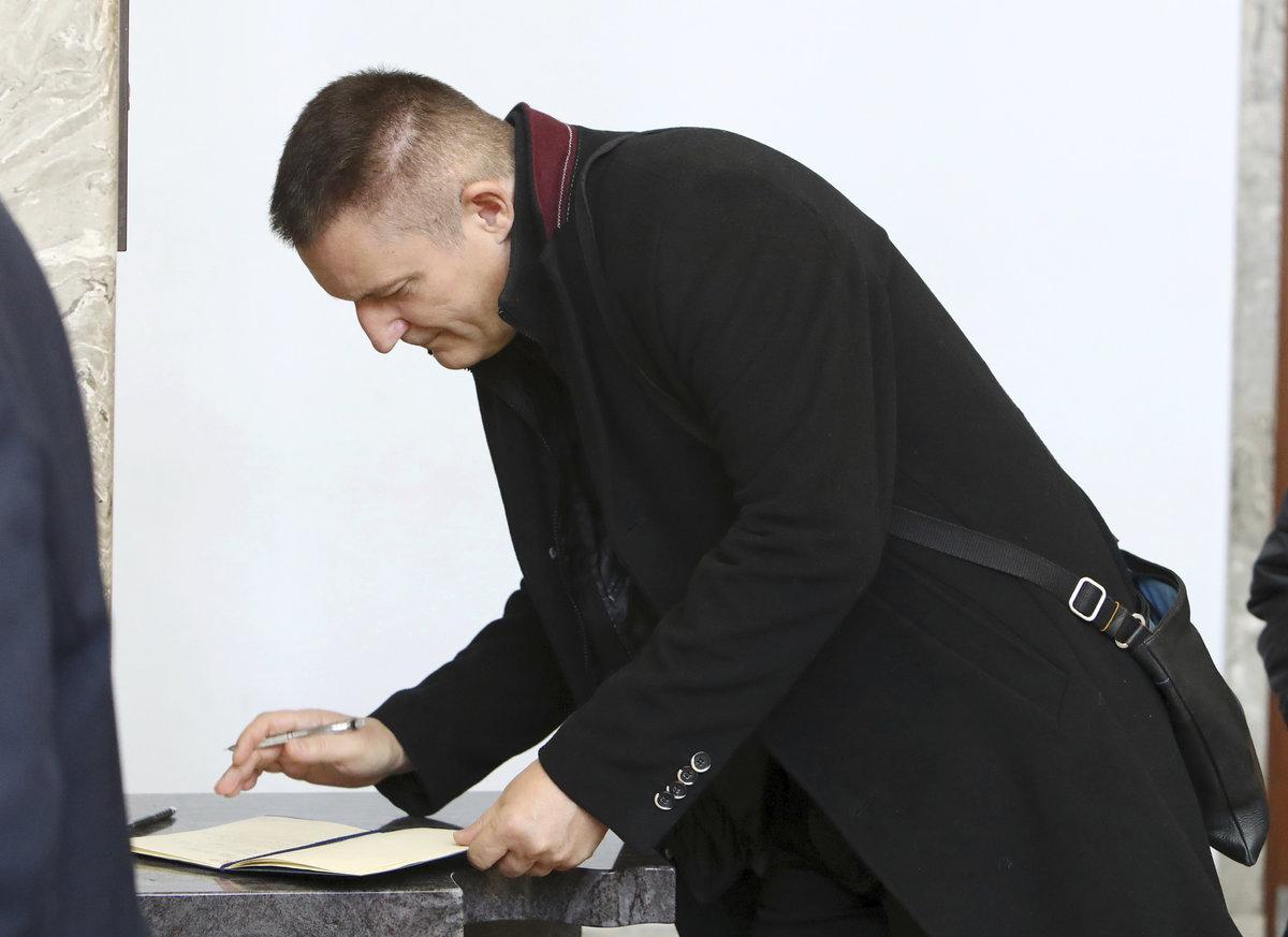 Vladimír Hron zapisuje do kondolenční knihy