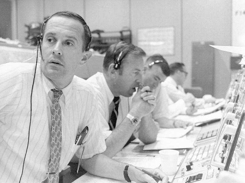 V řídicím středisku seděli také astronauti. Na obrázku je Charles Duke v roli tzv. Capcomu, což je člověk, který komunikoval přímo s posádkou. Dále jsou na snímku Jim Lovell a Fred Haise, kteří byli záložní posádkou Apolla 11