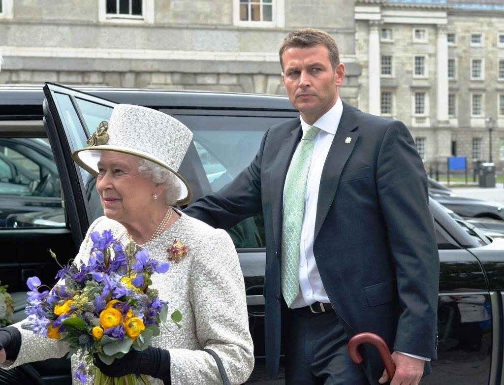Královna s jedním ze členů početné ochranky.