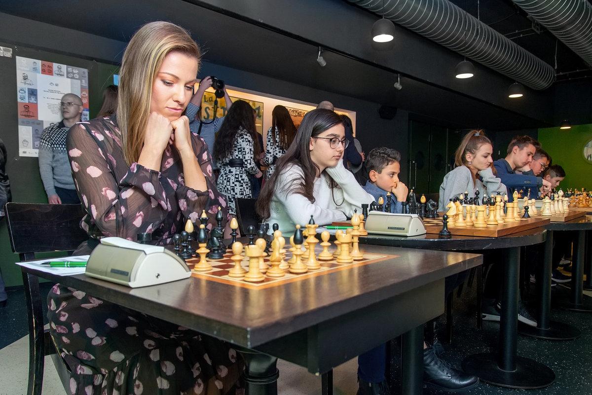 Inna se soustředí nad šachovnicí.