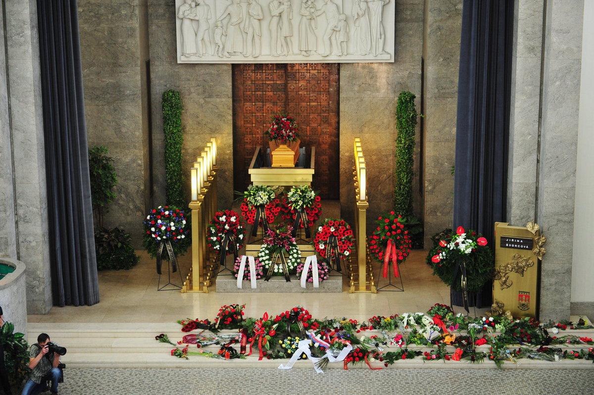 Katafalk s rakví Švorcové je obložen věnci a květinami