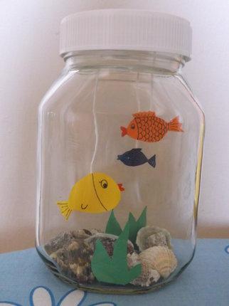 Do sklenice vsypeme mušle, písek či kamínky, vložíme vystřižené vodní rostliny. Zavíčkujeme a je hotovo.