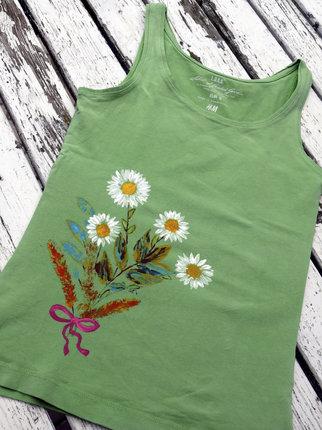 Trávy a květiny natřeme barvou a pak otiskneme na tričko, případně domalujeme. Konečnou úpravou je fixování barev přes pečicí papír žehličkou.