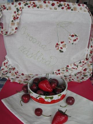 Tužkou si předkreslíme nápis a vyšijeme jej zelenou vyšívací bavlnkou. Rovněž vyšijeme stonek k našitým třešním. Zástěra připomíná kuchyň z doby našich babiček, díky svému ovocnému motivu bude hezkým doplňkem letní kuchyně.
