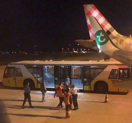 Obrázek pořízený jedním z cestujících ukazuje, jak zdravotní personál doprovází muže z letadla do autobusu.