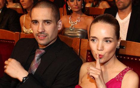 Pssst! Tomáš o tom ještě neví, jakoby naznačovala Lucie.