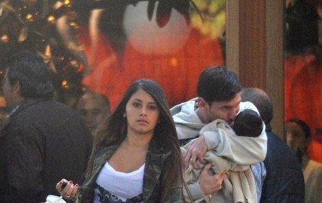 Rodinná procházka. Taťka Lionel líbá Thiaga a Antonella tlačí kočárek.