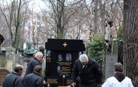 Příbuzní a přátelé ukládají rakev do rodinné hrobky.