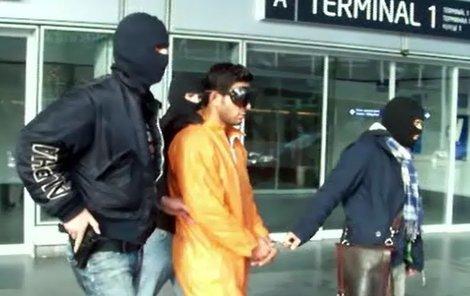 Kriminalisté odvádějí zadrženého cizince z letiště.