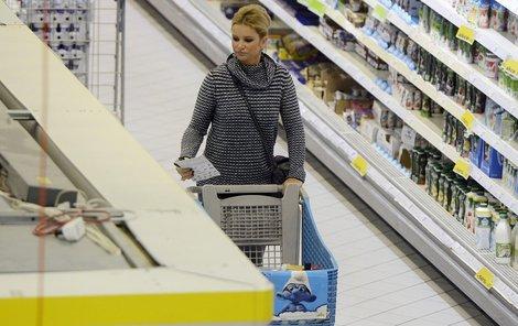 Monika Babišová mezi regály s košíkem a s papírem, na němž je nejspíš seznam potřebného trvanlivého zboží potřebným.