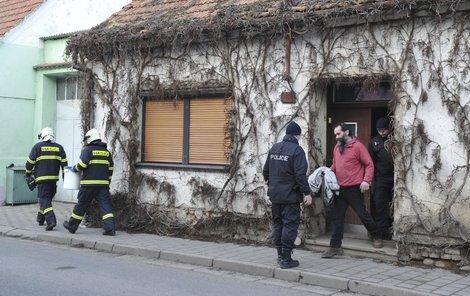 Muže v červené mikině včera policisté z domu odvedli.