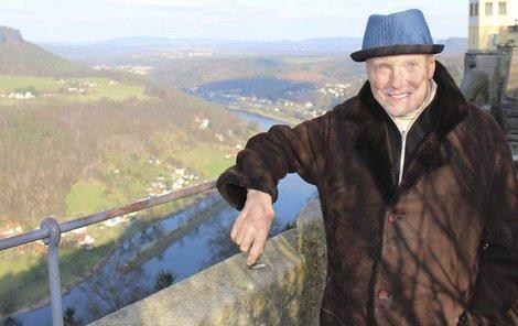 Za zpěvákem je vidět jedna z věžiček pevnosti Königstein, která leží nad řekou Labe.
