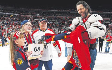 Vysmátý Jaromír Jágr odevzdává svůj dres šťastné fanynce a jejím blízkým.