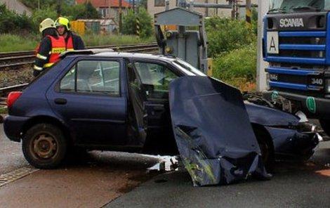 Po ťukanci do vlaku skončilo auto zapasované pod náklaďákem.