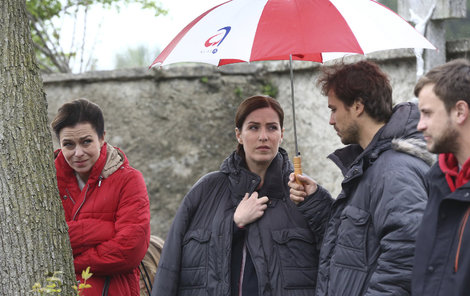 Norisová s kolegy v dešti a v bundách.