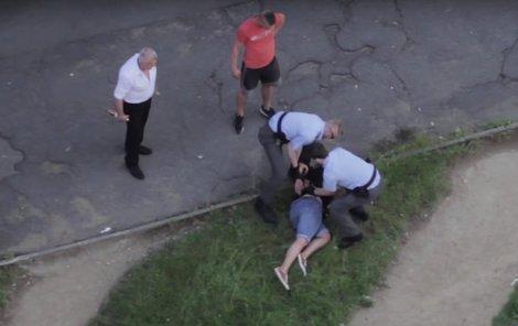 Tady už ji policisté nasazují pouta.