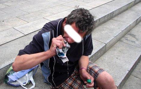 Bezdomovec si noviny nasáklé vínem vymačkává do úst.