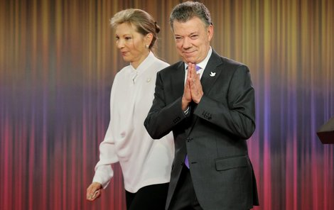 Dojatý Santos se ženou za zády.