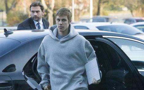 Justin vystupuje z auta a vyplazuje jazyk.