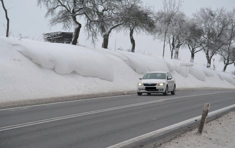 Závěje u obce Hosov se přelévají na silnici, zásněžky odpočívají složené za jedním ze stromů.