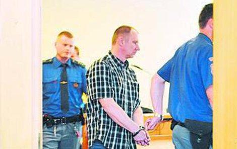 Přemysl Dlugi byl k soudu přepraven z věznice v poutech.