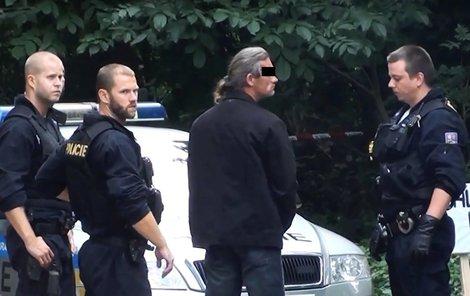 Údajný pachatel. Policisté ho přivezli na místo činu.