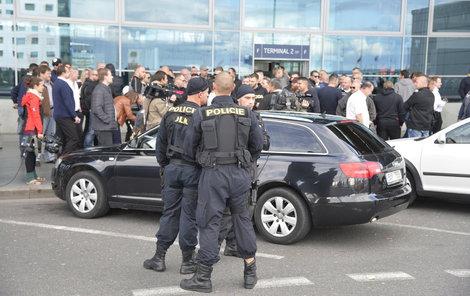 Taxikáře na letišti v Praze krotí policisté. Na vozy řidičů Uberu letí samolepky s nápisem Ilegal Transport.