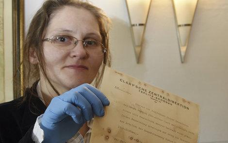 Restaurátorka Kateřina Dlabačová drží v ruce dokument, který s podpisem Antona Gustava Nosseka.