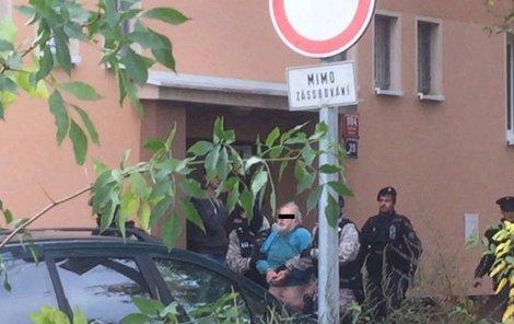 Muže policisté vyvedli s pouty na rukou...
