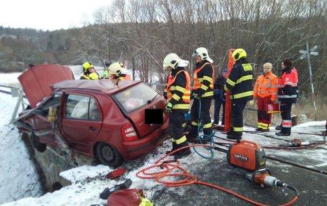 Auto po střetu zůstalo viset z mostu u trati...