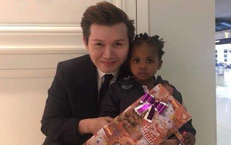 Dvouletá holčička Mashia, nejmladší členka rodiny, s dárkem, který jí na Vánoce dal zaměstnanec letiště.