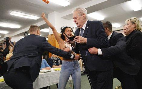 Žena zaútočila ve chvíli, kdy prezident chtěl ukázat komisi občanský průkaz.  A zatímco Ivana Zemanová i samotný prezident byli viditelně vyděšení, hradní protokolář Kruliš se jen usmíval.