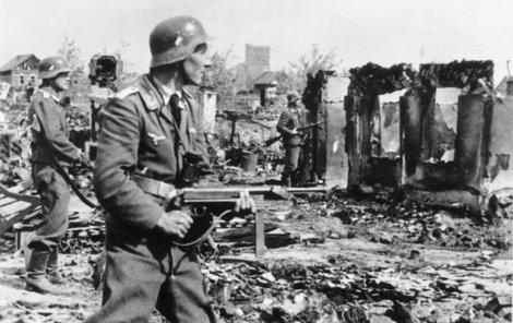 Příslušníci Wehrmachtu postupují ruinami města.