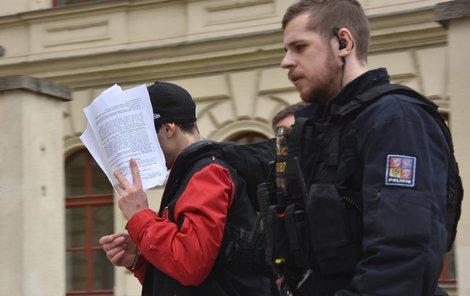 Mladý násilník (21) skončil ve vazbě. Při odchodu od soudu si zakrýval tvář.