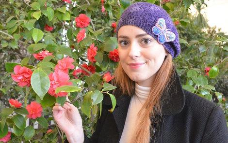 Studentka Marie Šínová u kamélií s červenými plnými květy.