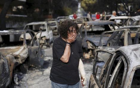 Zoufalá žena hledá v troskách ohořelých aut pejska.