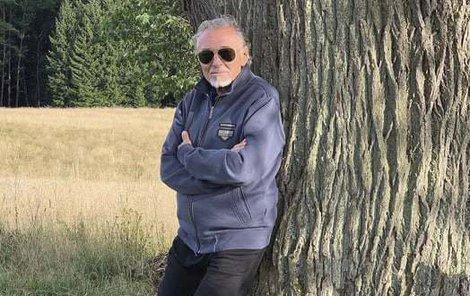 Karel na snímku relaxuje opřený o strom. Oblečený je v mikině, černých kalhotách a teniskách.