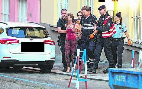 Zakrvácenou ženu odvedli policisté do sanitky.