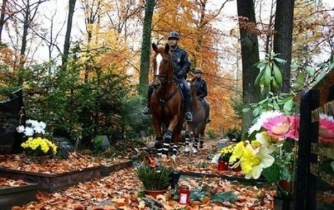 Policisté na koních vypadají mezi hroby jako andělé strážní.