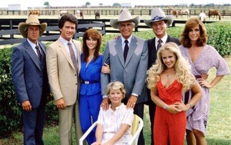 Ewingové v plné síle: zleva Steve Kanaly (63), Patrick Duffy (60), Victoria Principal (59), Jim Davis (†71, zemřel v roce 1981), Larry Hagman (78), Charlene Tilton (50), Linda Gray (69), v křesle Barbara Bel Geddes (†82, zemřela v roce 2005).