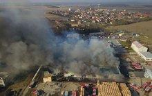 Mohutný požár včera zachvátil halu bývalých mrazíren v Mochově. Škoda je 100 milionů, hasičům komplikoval zásah nedostatek vody a ztížený přístup.
