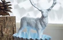 POTŘEBUJETE: kovové formičky, šišky, dřevěné špalíčky a prkénka, svíčky, plastové miniaturky zvířátek, univerzální lepidlo, štětec, barva Primalex Fortissimo, sprej Ledové květy