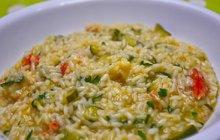 POTŘEBUJETE:olivový olej1 cibuli1 stroužek česneku60 g slaniny125 g rýže450 ml zeleninového vývaru1 cuketu1 lžíci másla2 lžíce strouhaného čedarusůlmletý pepř